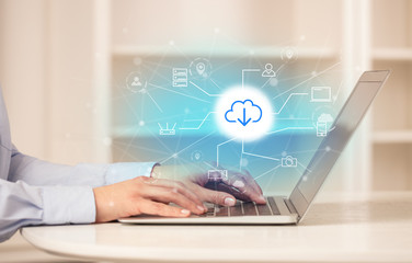 Business woman in homey environment using laptop with  online storage and cloud technology concept