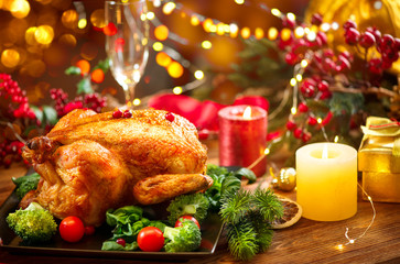 Christmas family dinner. Roasted chicken on holiday table, decorated with gift boxes, burning candles and garlands. Roasted turkey over wooden background