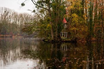 Petit kiosque ou gazébo sous une averse de pluie au bord d'un bois sur les berges d'un étang en automne en France