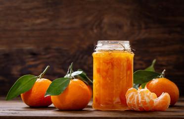 glass jar of tangerine jam with fresh fruits