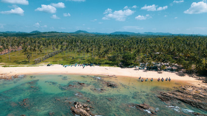 Aerial drone view of beautiful tropical island with sandy beach and green mountains. Summer and travel vacation concept