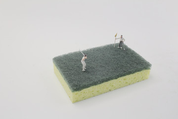 a mini figure play golf on sponge