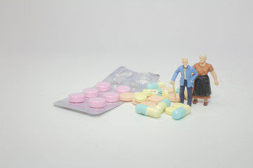 a small figure old man with pill