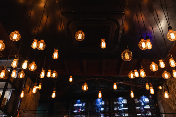 Many electrical lamps bulbs hanging from ceiling at restaurant interior and glowing in darkness. Dark background. Horizontal color photography.