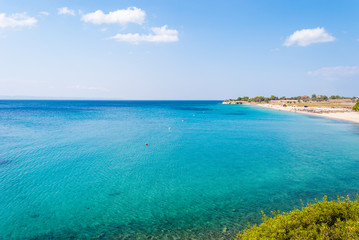 Sunny beautiful summer view of the sandy beach with Greek blue sea with shallow clean water and small rocks, Halkidiki Greece