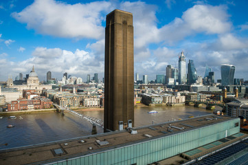 Brown brick tower of a former power station standing on the South Bank of the River Thames above the skyline of the City of London financial district