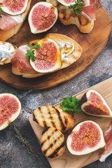 Prosciutto with figs . Fresh figs with ham and cheese on a grilled toast, rustic background. Appetizing snack. Top view,toned photo
