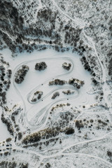 Aerial view to Motorcycle rider on snowy motocross track. Mx rider on snow. Motocross rider on bike, motocross winter season race. Drone view Racer motorcycle rides on motocross snowy track in winter.