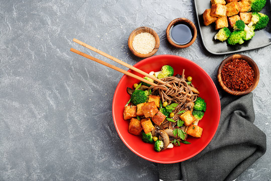 Soba noodles with vegetables and fried tofu in a bowl. Top view.