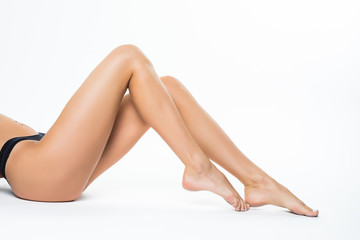 The young woman with perfect body touching her smooth silky legs after depilaton isolated on a white background.