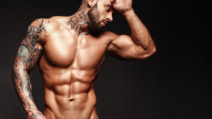 Banner image of sexy man with muscular body. Portrait of sexi male model. Hot macho, bodybuilder with muscle torso in abs poses on black background. 16 in 9 crop for design