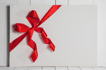 Red ribbon bow on white board