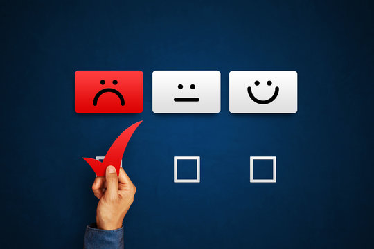 Hand of client show a feedback with bad smile face card. Service rating, satisfaction concept
