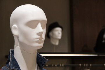 White male mannequin's head with another male mannequin's head in black hat in the background