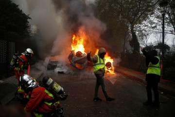 Protesters wearing yellow vests, a symbol of a French drivers' protest against higher diesel fuel taxes, gather near a burning car during clashes near the Place de l'Etoile in Paris