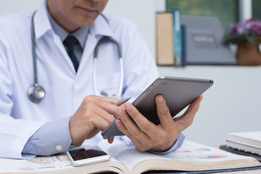 Doctor using digital tablet and reading book