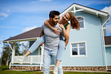 Young man giving his cheerful girlfriend piggyback on background of their new house