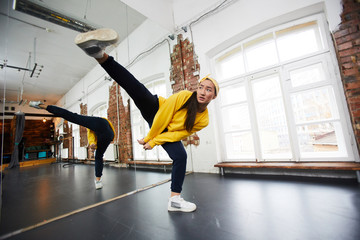 Young hip hop dancer in activewear stretching right leg while standing on the left one during training