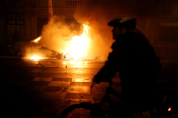 """A man cycles past a burning car during clashes as part of a demonstration by """"yellow vests"""" protesters near the Place de l'Etoile in Paris"""
