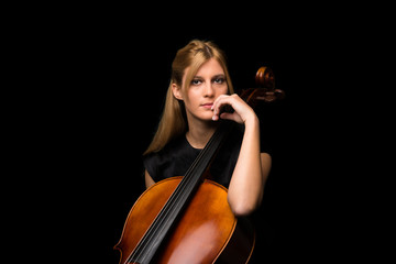 Young girl playing the cello on isolated black background Wall mural