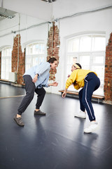 Breakdance trainer and her learner training together in front of one another in studio