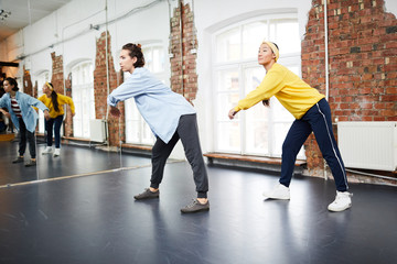 Contemporary girls in activewear practicing hip hop dancing while training in studio