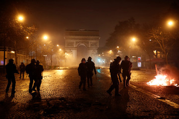 French riot police stand guard near the Arc de Triomphe during clashes with protesters wearing yellow vests, a symbol of a French drivers' protest against higher diesel taxes, in Paris