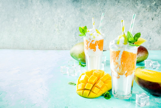 Tropical sweet dessert drink. mango milkshake or smoothie cocktail, with mango slices, mint and ice cubes, light blue background copy space