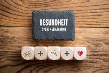 """Gesundheitssymbole auf Würfeln und das Wort """"Gesundheit - Sport + Ernährung"""" auf Schiefertafel"""