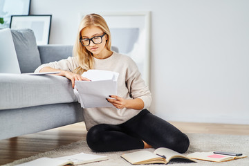 Female student sitting on floor at home with books and notes studying