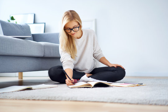 Female student sitting on floor in living room studying with books and making notes