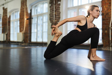 Active and flexible girl in black activewear stretching on the floor during training