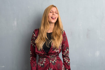 Blonde woman showing tongue at the camera having funny look on textured wall background