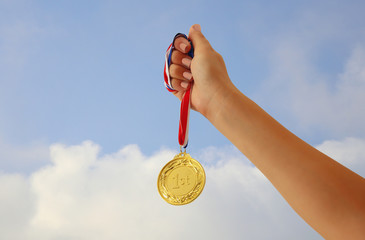 woman hand raised, holding gold medal against sky. award and victory concept.
