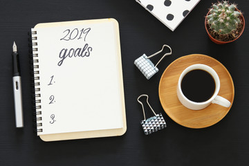 Top view 2019 goals list with notebook, cup of coffee over wooden black desk.