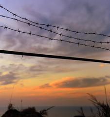 Farbenprächtiger Sonnenuntergang am Meer mit Stacheldrahtzaun