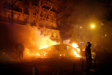 Firemen extinguish burning cars set afire by protesters wearing yellow vests, a symbol of a French drivers' protest against higher diesel fuel taxes, during clashes near the Place de l'Etoile in Paris