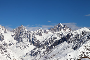 Rocky peaks of the mountains in snow and beautiful blue sky