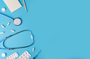 Medical concept blue background. Doctor's desk with instruments. Copy space.