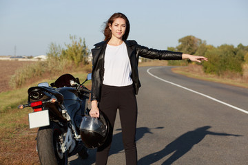 Outdoor shot of female biker hitchhikes on road, holds helmet in one hand, wears leather jacket, stops other transport, needs help, votes. Woman motorcyclist asks for help on roadside. Transport