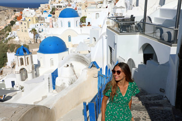 Happy travel tourist woman go upstairs in Santorini, Greek Islands, Greece, Europe. Girl on summer vacation visiting famous tourist destination having fun smiling in Oia.