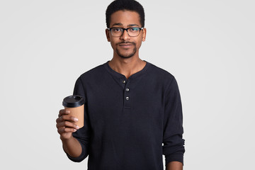 Horizontal shot of serious black young man holds takeaway coffee, wears transparent glasses, has break after work, models against white background, enjoys spare time. People and drinking concept