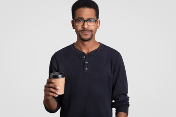 Sad serious black man with Afro haircut, wears spectacles, speaks with partner during coffee break, dressed in casual clothing, holds disposable cup of beverage, isolated over white background