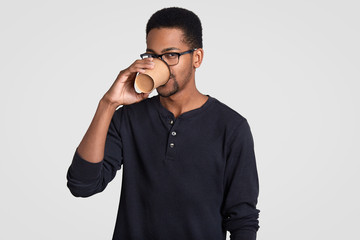 Photo of dark skinned guy with curly hair, drinks coffee from disposable cup, dressed in casual black sweater, spectacles, stands against white wall. African American student has break after classes