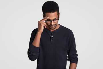 Stressful tired overworked male worker has dark skin, keeps hand on head, looks down, wears transparent glasses and casual jumper, tries to gather with thoughts, isolated over white background