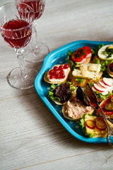 set of mini sandwiches or tapas for two with glasses of wine on a light wooden table