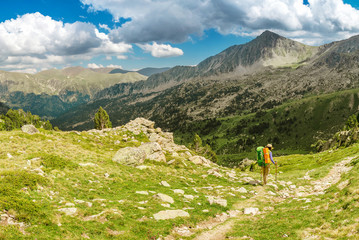 Happy woman hiker travels in Pyrenees Mountains in Andorra and Spain. Nordic walking, recreation and trekking along GR11 path trail
