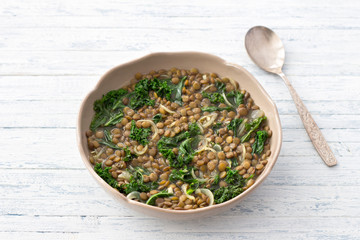 Stewed kale lentils with onions and garlic on a light background, selective focus, free space. Delicious homemade healthy food
