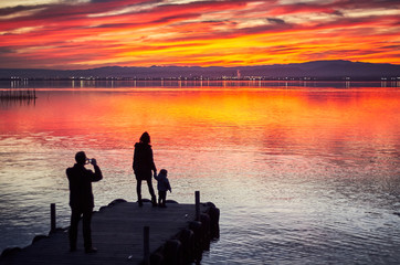 Family taking pictures in the sunset of the calm waters of the Albufera de Valencia, Spain.