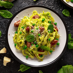 Homemade Pasta with green peas, spinach pesto and sausages. parmesan cheese. healthy food. background